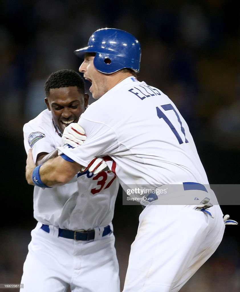 Elian Herrera #37 of the Los Angeles Dodgers is grabbed by A.J. Ellis #17 after Herrera hit a walk off RBI single in the ninth inning to defeat the San Francisco Giants on October 1, 2012 at Dodger Stadium in Los Angeles, California. The Dodgers won 3-2.