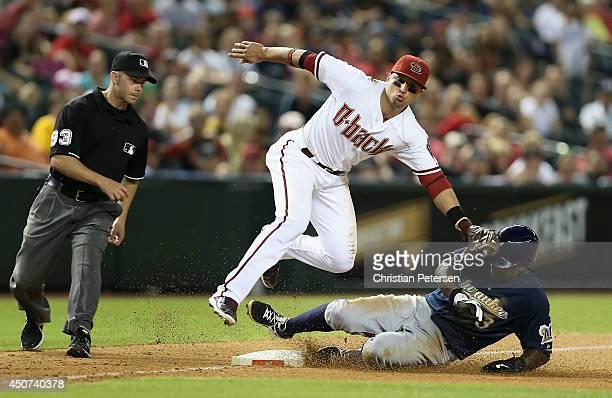 Elian Herrera of the Milwaukee Brewers safely steals third base under the tag from infielder Martin Prado of the Arizona Diamondbacks during the...