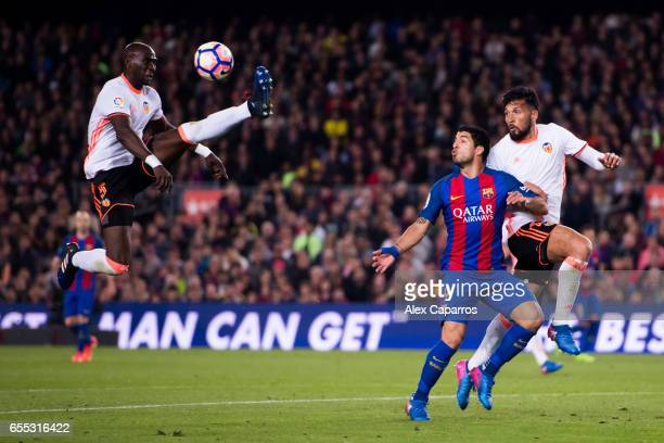 Eliaquim Mangala of Valencia CF controls the ball next to his teammate Ezequiel Garay and Luis Suarez of FC Barcelona during the La Liga match...