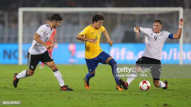 Elias Abouchabaka and JannFiete Arp of Germany battles for the ball with Victor Bobsin of Brazil during the FIFA U17 World Cup India 2017 Quarter...