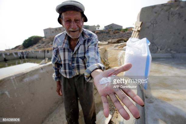 Elias alNajar displays salt flakes in the coastal Lebanese town of Anfeh north of the capital Beirut on July 21 2017 Traditional coastal salt...
