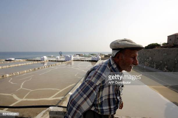 Elias alNajar walks past a salt evaporation pond in the coastal Lebanese town of Anfeh north of the capital Beirut on July 21 2017 Traditional...
