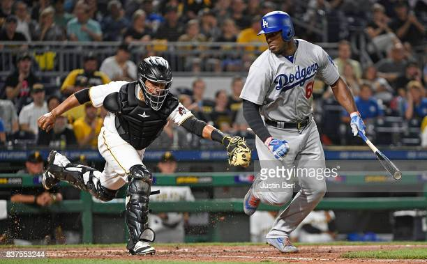 Elias Diaz of the Pittsburgh Pirates tags out Yasiel Puig of the Los Angeles Dodgers after a dropped third strike call in the fifth inning during the...