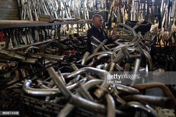 Elias Dube an employee of 34 years looks at some of the thousands of exhaust parts in stock at 'The Bike Hospital' on October 18 2017 in Johannesburg...