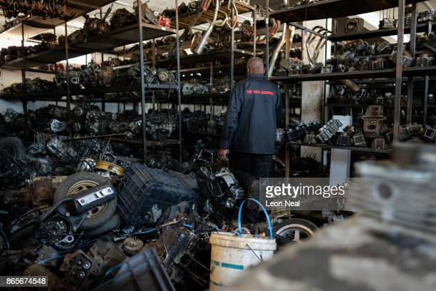 Elias Dube an employee of 34 years steps over some of the thousands of engines at 'The Bike Hospital' on October 18 2017 in Johannesburg South Africa...