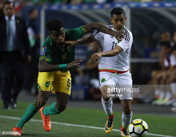 Elias Hernandez of Mexico fights for the ball with Alvas Powell of Jamaica during a Group C match between Mexico and Jamaica as part of CONCACAF Gold...