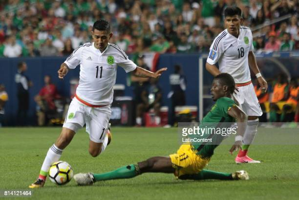 Elias Hernandez of Mexico fights for the ball with Cory Burke of Jamaica during a Group C match between Mexico and Jamaica as part of CONCACAF Gold...