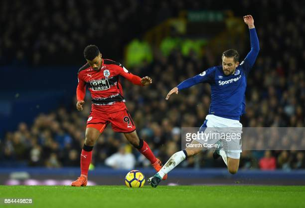 Elias Kachunga of Huddersfield Town is challenged by Gylfi Sigurdsson of Everton during the Premier League match between Everton and Huddersfield...