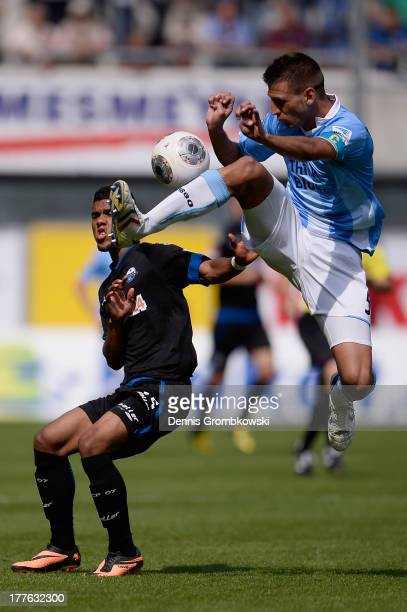 Elias Kachunga of SC Paderborn is challenged by Guillermo Vallori of 1860 Muenchen during the Second Bundesliga match between SC Paderborn and TSV...