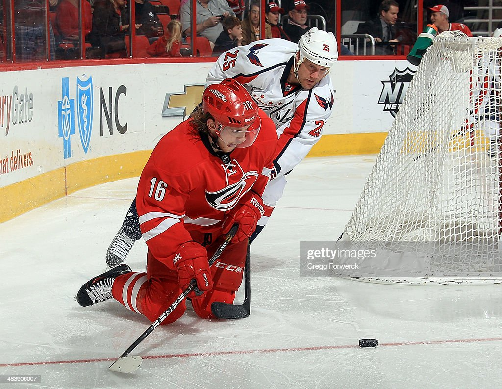 <a gi-track='captionPersonalityLinkClicked' href=/galleries/search?phrase=Elias+Lindholm&family=editorial&specificpeople=8613151 ng-click='$event.stopPropagation()'>Elias Lindholm</a> #16 of the Carolina Hurricanes attempts to play the puck from his knees while defended by <a gi-track='captionPersonalityLinkClicked' href=/galleries/search?phrase=Jason+Chimera&family=editorial&specificpeople=211264 ng-click='$event.stopPropagation()'>Jason Chimera</a> #25 of the Washington Capitals during their NHL game at PNC Arena on April 10, 2014 in Raleigh, North Carolina.