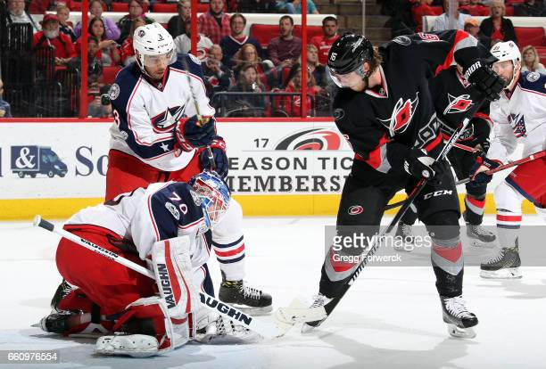 Elias Lindholm of the Carolina Hurricanes pokes at a puck covered by Joonas Korpisalo of the Columbus Blue Jackets during an NHL game on March 30...