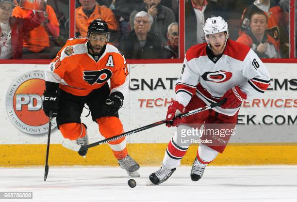 Elias Lindholm of the Carolina Hurricanes skates the puck against PierreEdouard Bellemare of the Philadelphia Flyers on April 9 2017 at the Wells...
