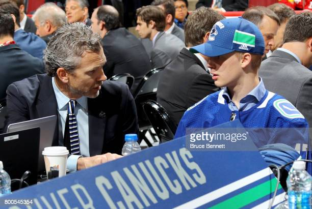 Elias Pettersson talks with Vancouver Canucks executives after being selected fifth overall during the 2017 NHL Draft at the United Center on June 24...