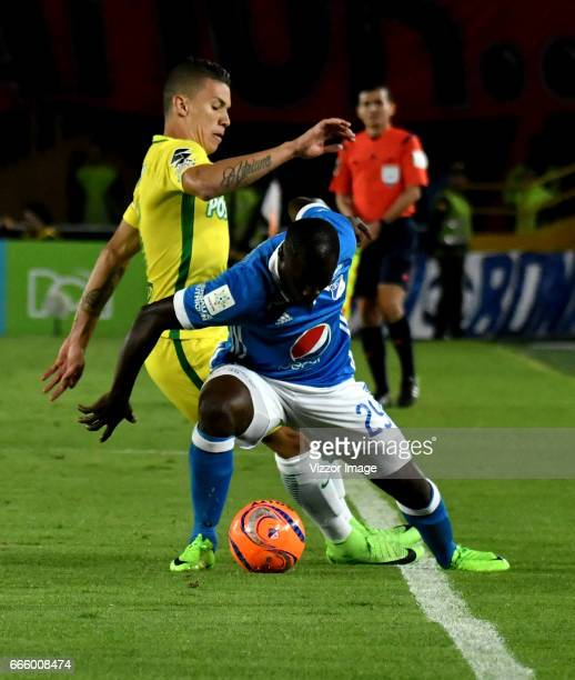 Elicer Quinones of Millonarios vies for the ball with Mateus Uribe of Atletico Nacional during the match between Millonarios and Atletico Nacional as...
