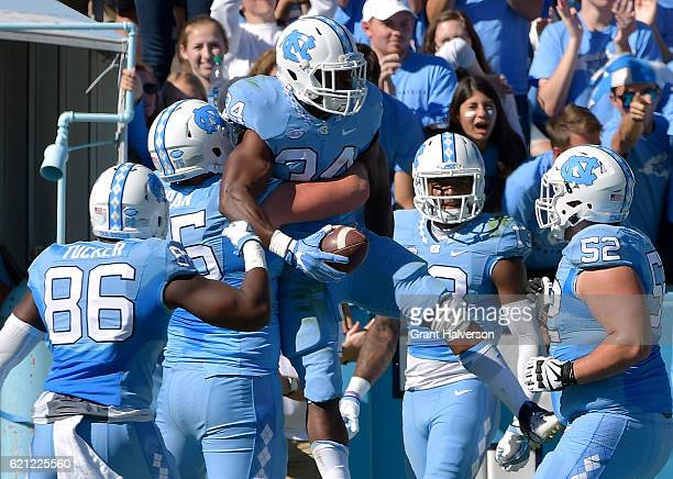 Elijah Hood of the North Carolina Tar Heels celebrates with teammates after scoring a touchdown against the Georgia Tech Yellow Jackets during the...