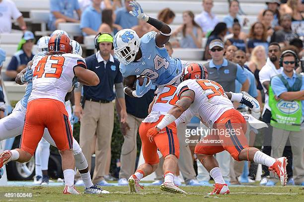 Elijah Hood of the North Carolina Tar Heels dives over Clayton Fejedelem of the Illinois Fighting Illini for extra yardage during their game at Kenan...