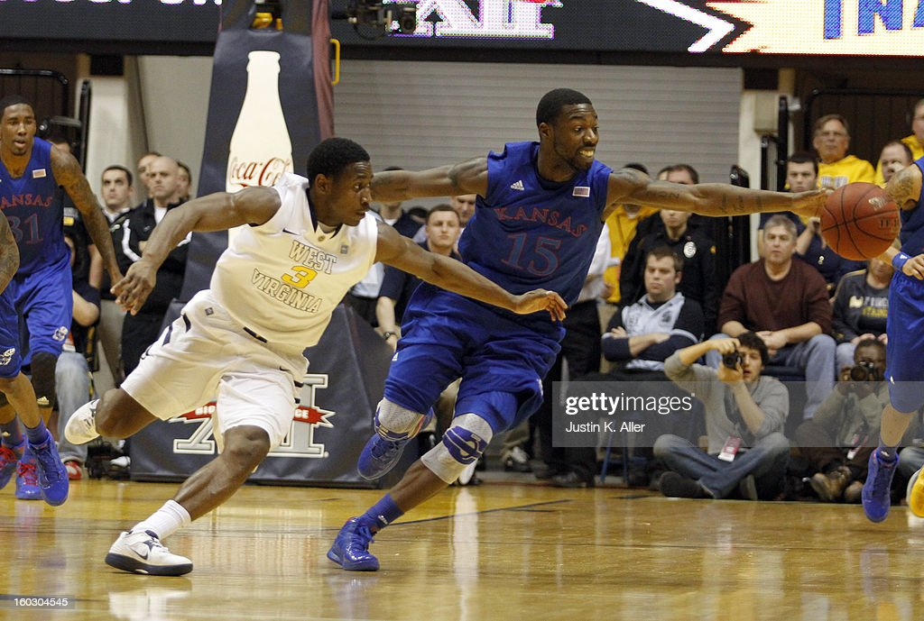 Elijah Johnson #15 of the Kansas Jayhawks battles for a loose ball with Juwan Staten #3 of the West Virginia Mountaineers at the WVU Coliseum on January 28, 2013 in Morgantown, West Virginia.