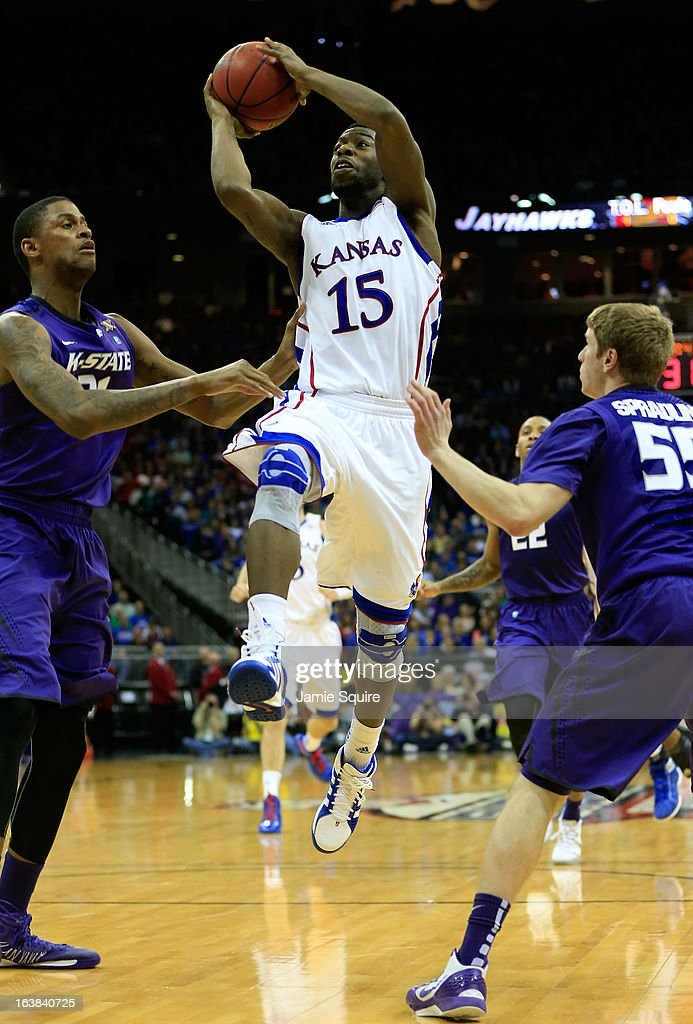 Elijah Johnson #15 of the Kansas Jayhawks shoots against Jordan Henriquez #21 and Will Spradling #55 of the Kansas State Wildcats in the second half during the Final of the Big 12 basketball tournament at Sprint Center on March 16, 2013 in Kansas City, Missouri.