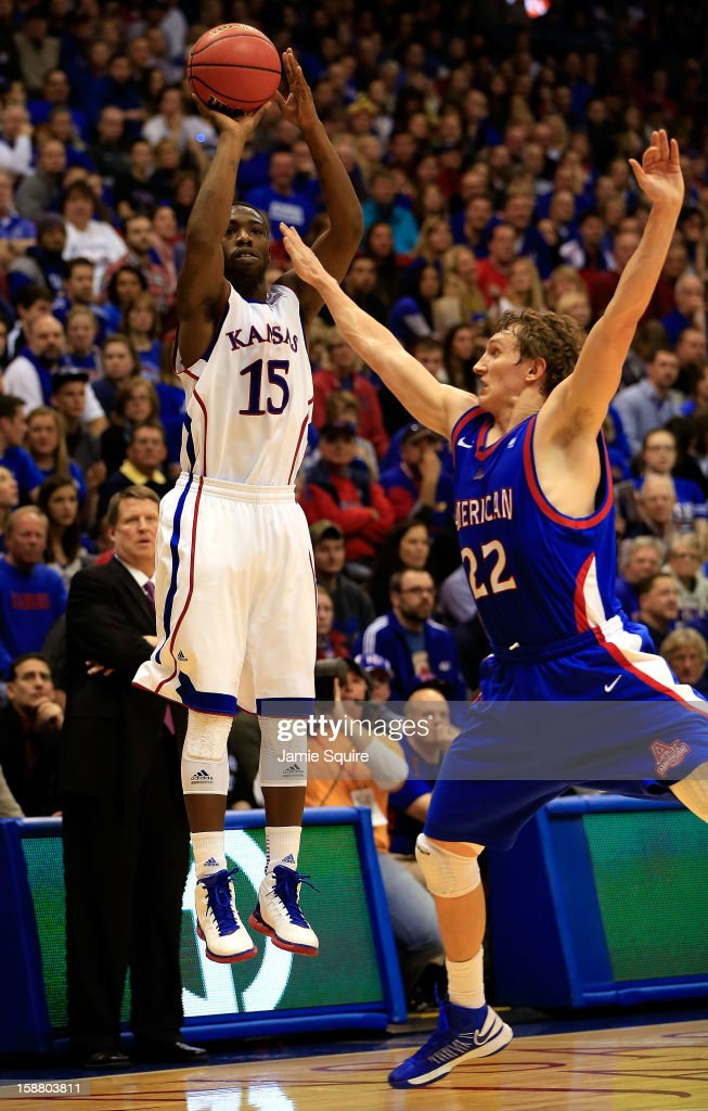 Elijah Johnson #15 of the Kansas Jayhawks shoots over John Schoof #22 of the American University Eagles during the game at Allen Fieldhouse on December 29, 2012 in Lawrence, Kansas.