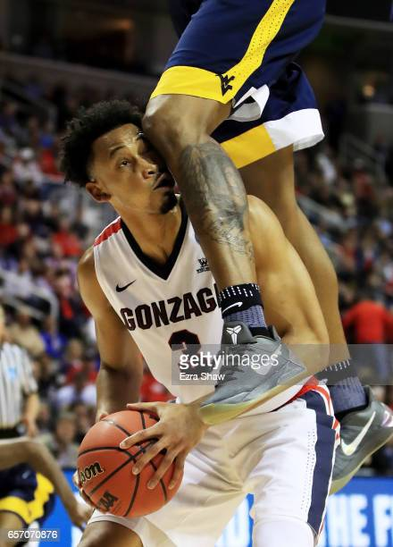 Elijah Macon of the West Virginia Mountaineers comes down on top of Johnathan Williams of the Gonzaga Bulldogs in the second half during the 2017...