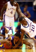 Elijah Muhammad of the Tennessee Tech Golden Eagles battles Tyshawn Taylor of the Kansas Jayhawks for a loose ball during the game on November 27...