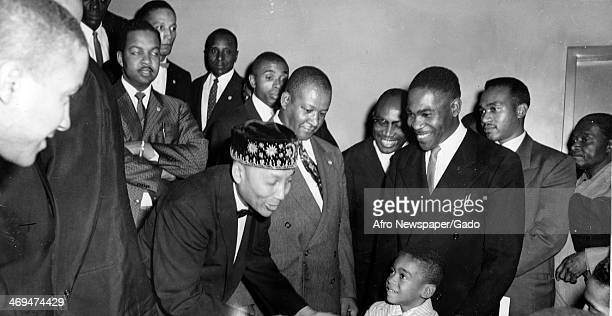 Elijah Muhammad the leader of Nation of Islam addressing a young boy surrounded by a group of men Boston Massachusetts 1963