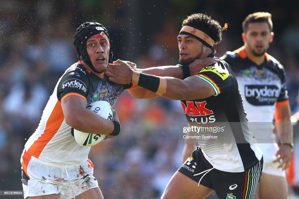 Elijah Taylor of the Tigers is tackled during the round two NRL match between the Wests Tigers and the Penrith Panthers at Campbelltown Sports Stadium on March 12, 2017 in Sydney, Australia.