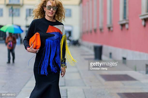Elina Halimi wearing a Christopher Kane sweater with finges black skirt and orange bag outside Missoni during the Milan Men's Fashion Week...