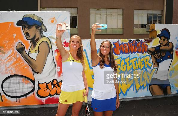 Elina Svitolina of Ukraine and Monica Puig of Puerto Rico take selfies after painting street art with Melbourne graffiti artist Daniel Wenn during...