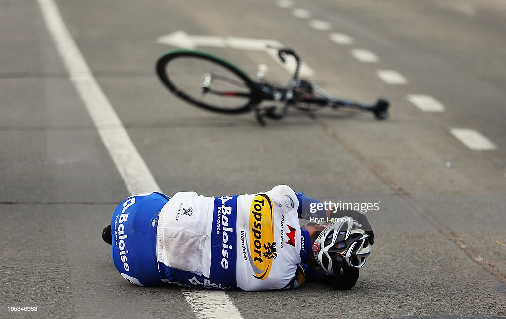 Eliot Lietaer of Belgium and Topsport Vlaanderen - Baloise lies on the ground after crashing during the 97th Tour of Flanders from Brugge to Oudenaarde on March 31, 2013 in Bruges, Belgium.