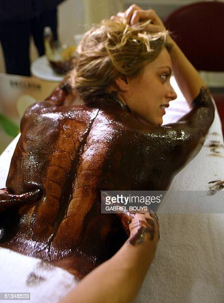 Elisa Bocchini from Spoleto central Italy has a chocolate massage at a beauty therapy stand during the Eurochocolate 2002 festival 23 October 2002 in...