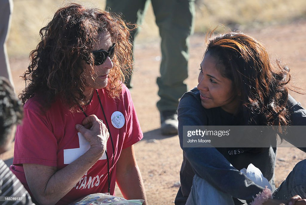 Elisa Hauptman (L), a volunteer for the non-profit Samaritans group, speaks with a detained 20-year-old Mexican immigrant as a U.S. Border Patrolman stands guard on March 6, 2013 near Walker Canyon, Arizona. Due to broad federal sequestration budget cuts, Border Patrol agents are expected to begin taking unpaid furlough days in April, as Customs and Border Protection funding is reduced by more than $500 million.