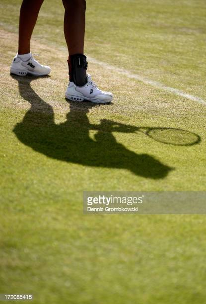Elise Mertens of Belgium's shadow is cast on the grass during the Girls' Singles first round match against Carolina Meligeni Rodrigues Alves of...