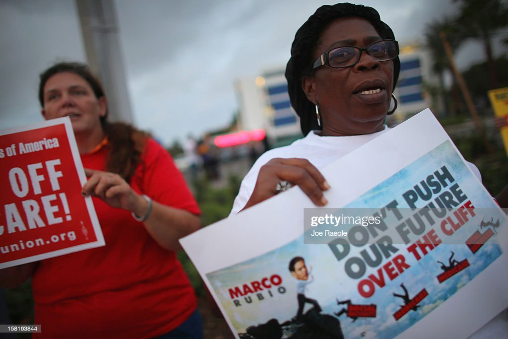 Elise Pierre along with other protesters rally together outside the office of U.S. Sen. Marco Rubio (R-FL) on December 10, 2012 in Doral, Florida. The protesters are hoping that Senators like Rubio will not cut medicare/social security benefits and will agree to raise taxes on the top 2% of earners in the country.