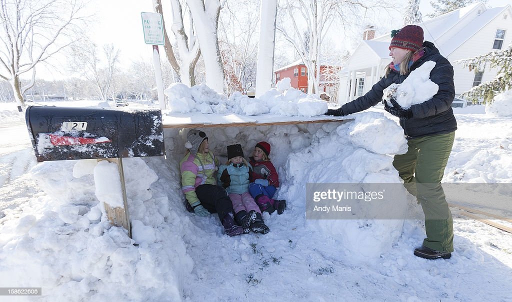 Elise Schmitt, left, 10, Julia Schmitt, 6, and their cousin Willa Treichel, right, 6, check out their newly made snow fort as Ellie Schmitt adds snow to the roof December 21, 2012 in Madison, Wisconsin. A day after a record snow storm hit Wisconsin, schools were closed Thursday and Friday.