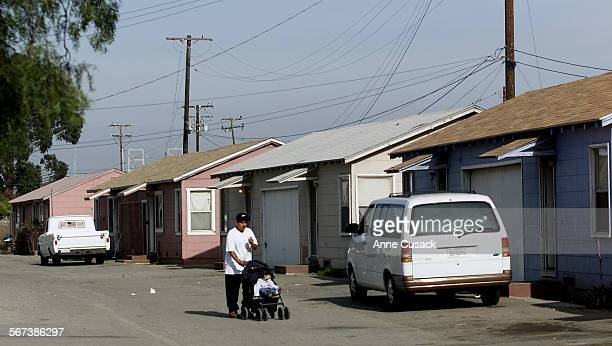 Eliseo Cortez walks his nephew Frankie Cortez age 1 by the farm worker housing in south Oxnard along Hueneme Road The housing will be torn down and...