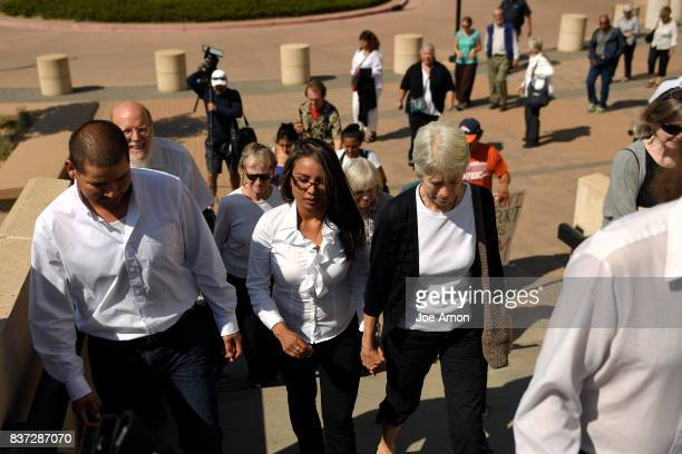 Eliseo Jurado and his partner Ingrid Encalada Latorre surrounded by Metro Denver Sanctuary Coalition members leave the Jefferson County Courthouse...