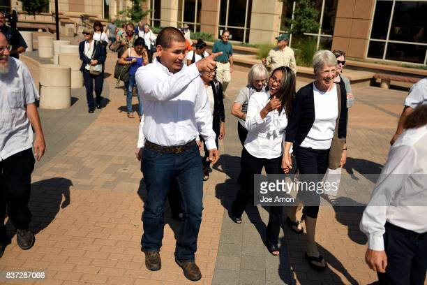 Eliseo Jurado points the way to their truck as he and his partner Ingrid Encalada Latorre surrounded by Metro Denver Sanctuary Coalition members...