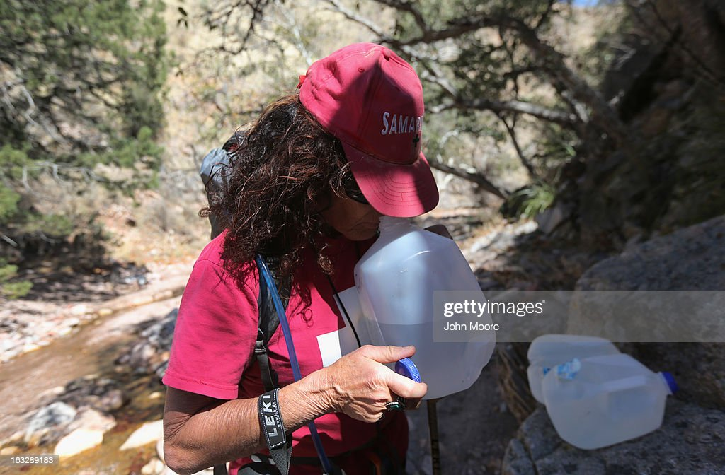 Elissa Hauptman, a volunteer for the non-profit Samaritans sniffs an old bottle of water near an immigrant trail near the Mexican border on March 6, 2013 in Walker Canyon, Arizona. The Samaritans group distributes fresh jugs of water along the trails with the aim of reducing immigrant deaths due to dehydration during their long trek from Mexico into the United States, often through remote desert areas.