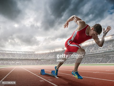 Elite 100m Runner Sprints From Blocks in Floodlit Stadium