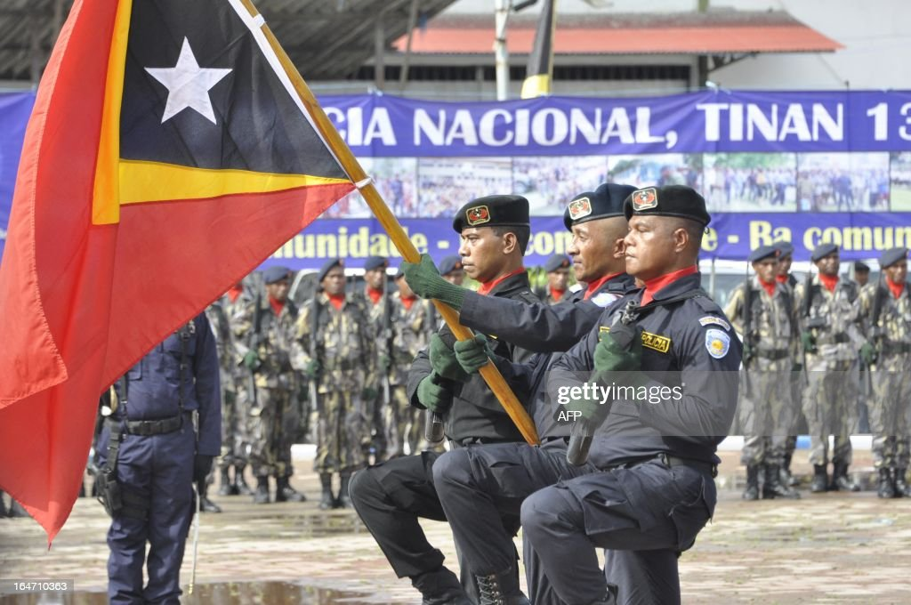 Elite East Timorese police commandos march with the national flag during the 13th anniversary celebration of the East Timor National Police (PNTL) in Dili on March 27, 2013. The UN ended its peacekeeping mission in December 2012 after 13 years in Asia's youngest nation following a bloody transition to independence after Indonesian occupation as the country faces the challenge of tackling rampant poverty. About a dozen police from Australia and Portugal remains in the police academy handling English language and other basic courses.