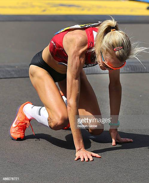 Elite women's runner Shalane Flanagan of the United States falls to her knees after she crossed the finish line of the 118th Boston Marathon on...