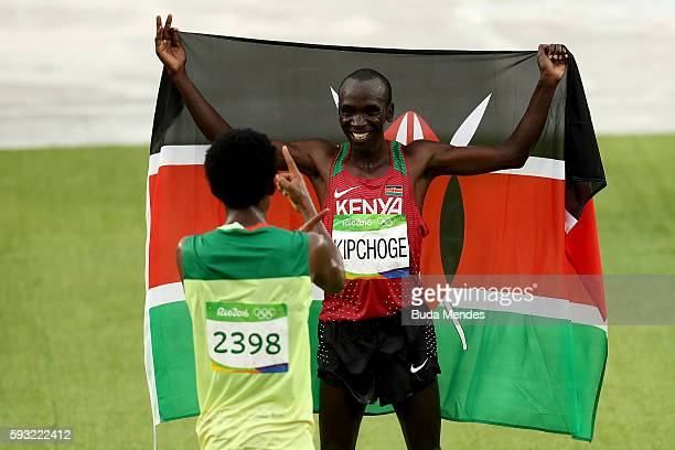 Eliud Kipchoge of Kenya celebrates as he wins gold with silver medalist Feyisa Lilesa of Ethiopia during the Men's Marathon on Day 16 of the Rio 2016...