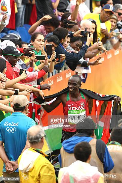Eliud Kipchoge of Kenya celebrates with spectators as he wins gold during the Men's Marathon on Day 16 of the Rio 2016 Olympic Games at Sambodromo on...