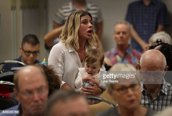Eliza Jacobs holding Sasha Dial reacts as Rep Brian Mast speaks during a town hall meeting at the Havert L Fenn Center on February 24 2017 in Fort...
