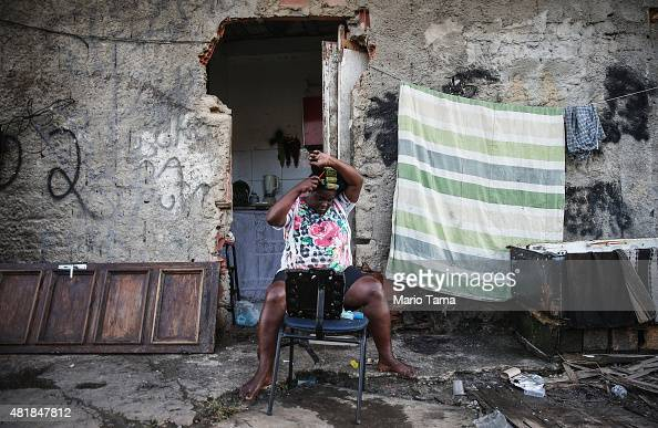 Elizabeta Queiroz curls her hair in front of her makeshift home amidst the rubble of destroyed homes in the MetroMangueira community or 'favela'...