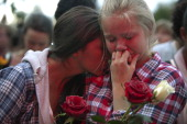 Elizabeth Amundsen and Tiril Killi comfort each other as thousands of people gather at a memorial vigil following Friday's twin extremist attacks on...
