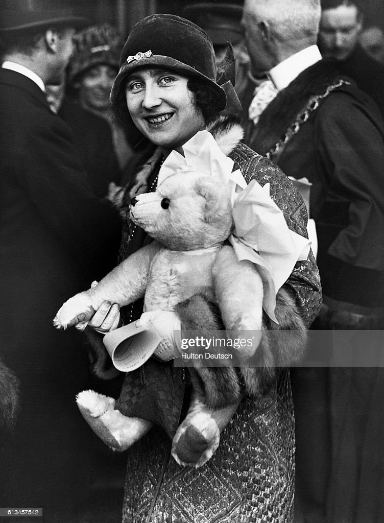 Elizabeth, Duchess of York, holds a teddy bear which is a gift for her daughter Princess Elizabeth (the future Queen Elizabeth II of England).