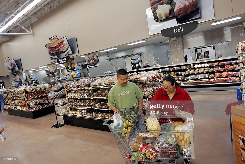 Elizabeth Gonzalez (R) and Silvestre Gonzalez load their shopping cart at the new 2,000 square foot Wal-Mart Supercenter store May 17, 2006 in Bowling Green, Ohio. The new store, one of three new supercenters opening today in Ohio, employs 340 people with 60 percent of those working full-time.