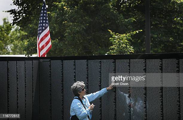 Elizabeth Hernandez touches her borthers name on the Moving Wall display a halfsize replica of the Vietnam Veterans Memorial following the opening...